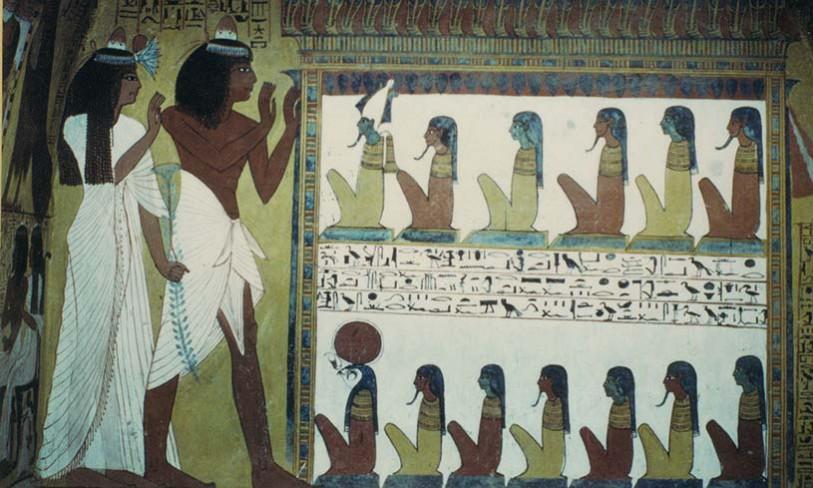 Der Grabherr Sennedjem steht mit seiner Frau Iyneferti anbetend für 13 Götter Ägyptens. Die obere Reihe mit fünf namenlosen Göttern führt der Gott Osiris an, erkennbar an der grünen Farbe seines Gesichts (weist auf seinen Status als Fruchtbarkeitsgott hin) und an der Atef-Krone mit den zwei Federn an den Seiten. In der unteren Reihe sitzt der falkenköpfige Gott Re-Harachte vor sechs Göttern, deren Namen ebenfalls nicht genannt werden. Die namenlosen Götter sind wahrscheinlich Götter des Totenreiches. © Martin Heinz Grab des Sennedjem (TT1), Theben-West Neues Reich, 19. Dynastie.