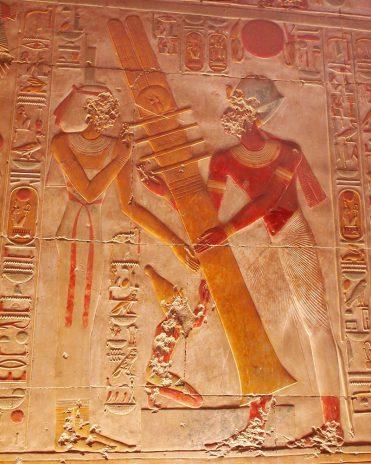 Der Djed-Pfeiler, ein Symbol für Stabilität und Dauer, galt als Wirbelsäule des Osiris. Hier richtet Pharao Sethos I. zusammen mit der Göttin Isis den Pfeiler auf. Das Aufrichten des Djed-Pfeilers galt Triumph Osiris gegen Seth. Tempel von Abydos, Neues Reich, 19. Dynastie