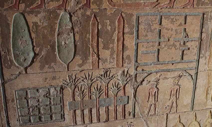 in den Gräbern der Beamten finden sich teils skurile Darstellungen von Häusern und Gärten, wie hier im Grab des Renini. Sein Haus ( oder ein Kultzentrum?) sollen die Strichlinien auf der rechten Seite darstellen. Es besteht aus sechs Räumen und unter dem Torbogen befinden sich zwei kultische Muu-Tänzer, die man an der hohen Kopfbedeckung erkennen kann. Vor dem Haus befindet sich ein Gewässer (das längliche Rechteck), das mit Palmen gesäumt ist. Die 16 Quadrate links könnten vielleicht bewässerte Felder darstellen. Im oberen Register verewigte der Künstler noch zwei Bäume und zwei Obelisken. Grab des Renini, el-Kab Neues Reich, 18. Dynastie