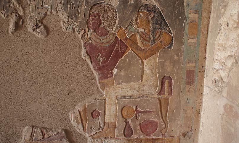 Das weibliche Schönheitsideal war ein blasser Teint. Daher tragen Frauen auf Abbildungen meistens eine hellere, ockergelbe Hautfarbe, während die Männer einen rotbraunen, dunklen Teint haben. Idy hält ihrem Gatten Renini liebevoll den Arm um die Schulter, während sie an einer Lotusblüte schnuppert. Griffbereit unter ihrem Stuhl befinden sich ein Hathorspiegel mit Kupferscheibe und Töpfe von Salben und Make-Up. Grab des Renini, el-Kab Neues Reich, 18. Dynastie