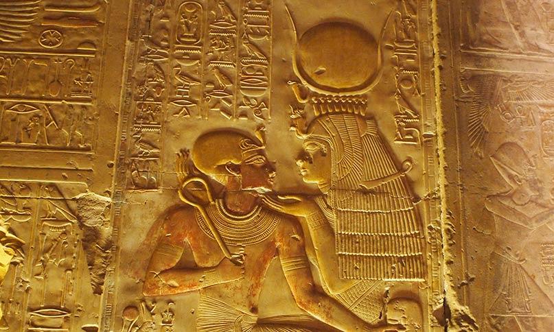 Isis mit Kuhgehörn und Sonnenscheibe. Auf ihrem Schoß sitzt der kleine Sethos I. Tempel von Abydos Neues Reich, 19. Dynastie