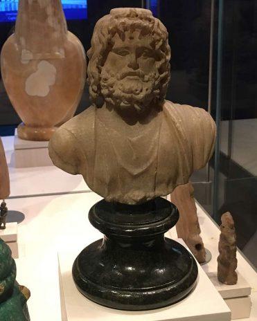 Der Gott Serapis, der sich aus den ägyptischen Göttern AOsiris, Apis und Amun zusammensetzt. Auch die Attribute der griechischen Götter Zeus und Asclepius vereinen sich in ihm Reichmuseum von Leiden, Niederlande